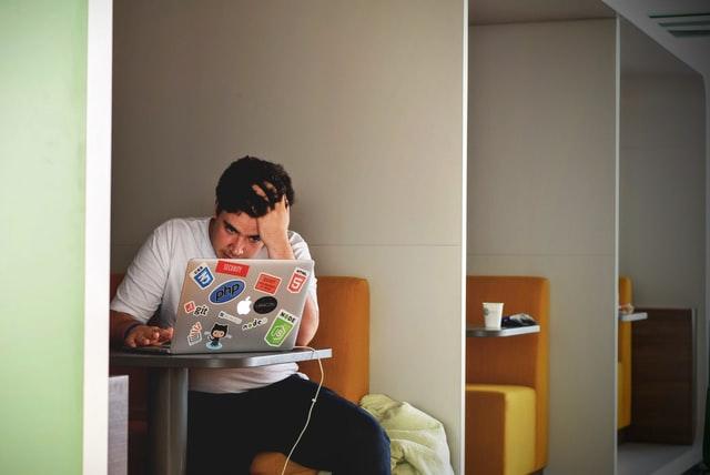 Junger Mann sitzt mit Problem vor Laptop