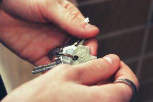 Zwei Hände halten Schlüssel für Mietwohnung